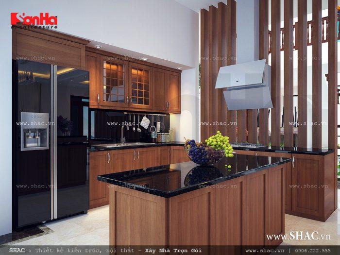 Nội thất gỗ lên ngôi trong phòng bếp biệt thự hiện đại 3 tầng tại Kiên Giang với gam màu trầm ấm kết hợp với mặt đá đen sáng bóng cho không gian bếp gọn gàng và sạch sẽ