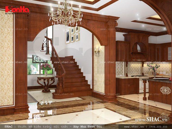 Ngăn cách giữa không gian phòng khách và phòng bếp ăn của ngôi biệt thự là sảnh thang được đầu tư thiết kế nội thất gỗ đẹp