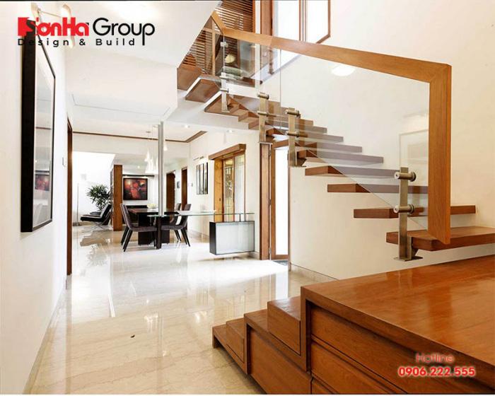 Sự kết hợp của chất liệu gỗ và kính làm nên mẫu cầu thang nhà ống đẹp
